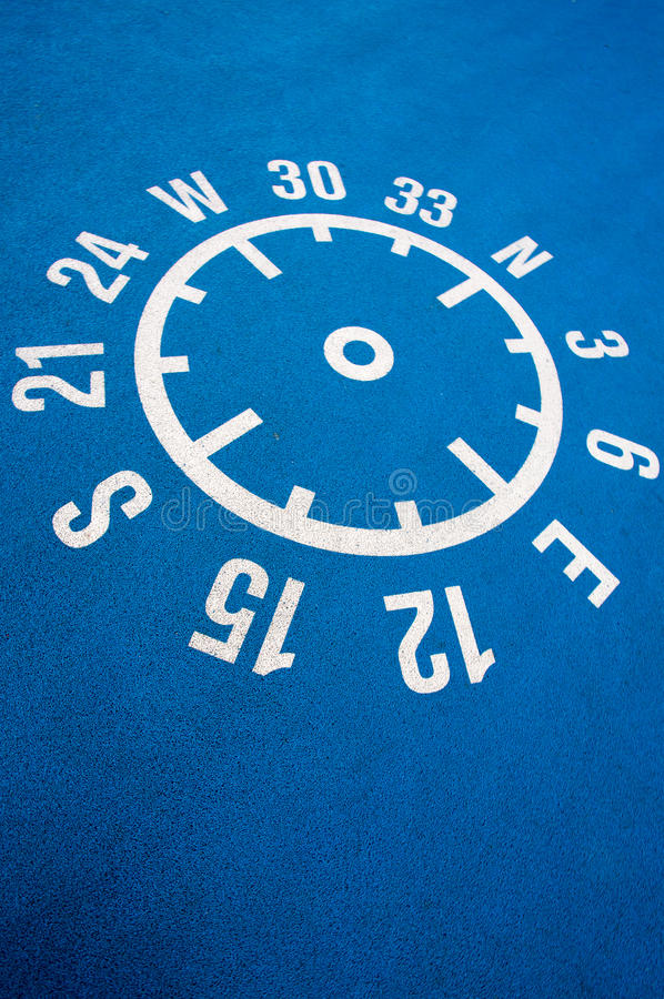 Floor compass with coordinates on the floor. White shape of compass printed with coordinates and numbers on a blue clean concrete floor royalty free stock images