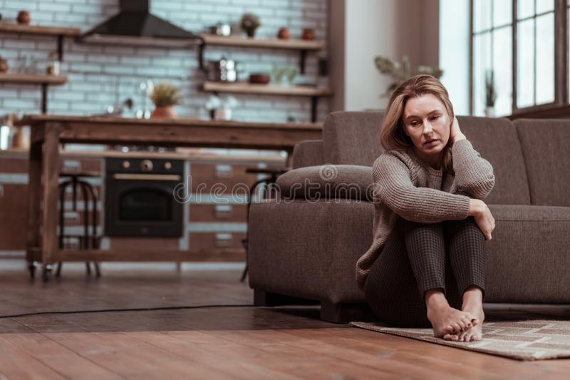 Depressed wife sitting on the floor while feeling stressed. On the floor. Depressed mature wife sitting on the floor while feeling stressed after family argument stock image