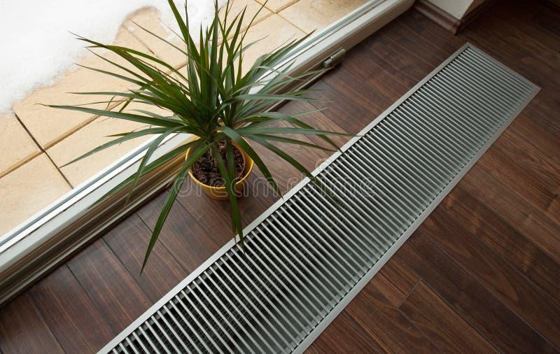 Floor heating. Underfloor heating recessed into the floor near the window royalty free stock photo