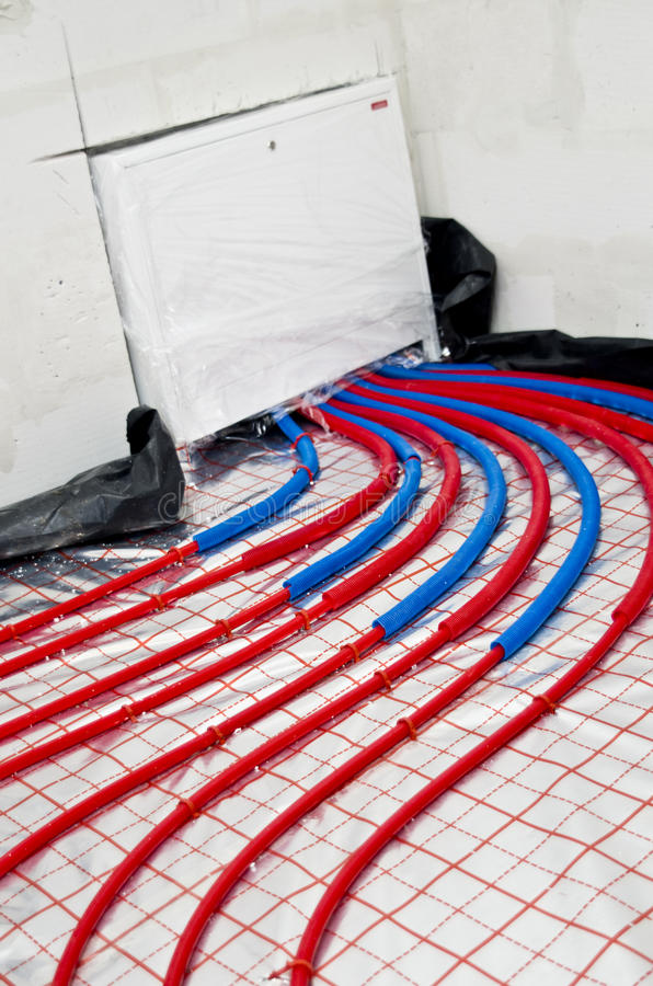 Floor heating installation. Red, plastic pipes of floor heating, with reflective foil. House building and renovation stage royalty free stock image