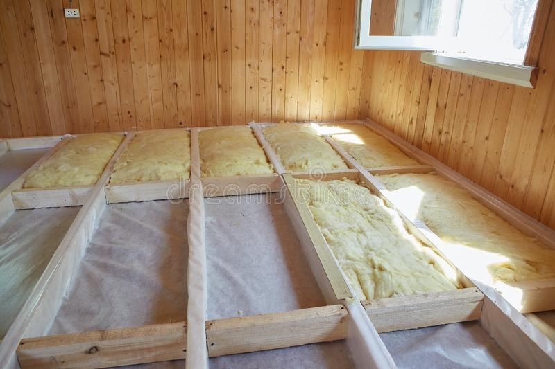 Floor heating insulation. Fitting thermal insulation layer under the floor with using mineral wool in the room of the country house. Stage-by-stage warming of a stock photography