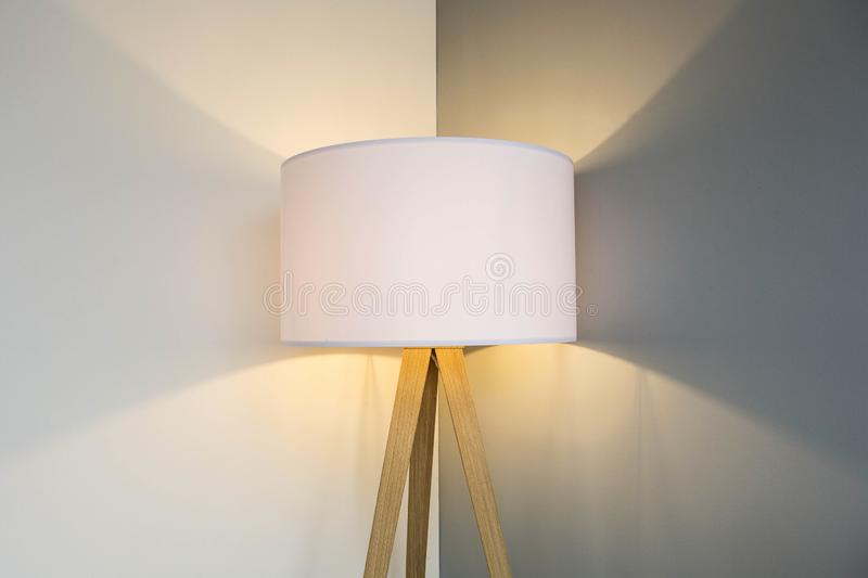 Floor lamp standing near white grey wall with big lamp shade modern design, symmetrical light background texture royalty free stock images