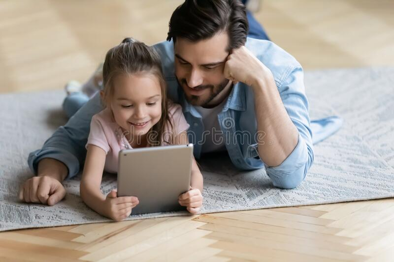 On floor lying daughter with father watching cartoons using tablet. On carpet lying little daughter with father watching cartoons using tablet gadget. Warm floor royalty free stock photo