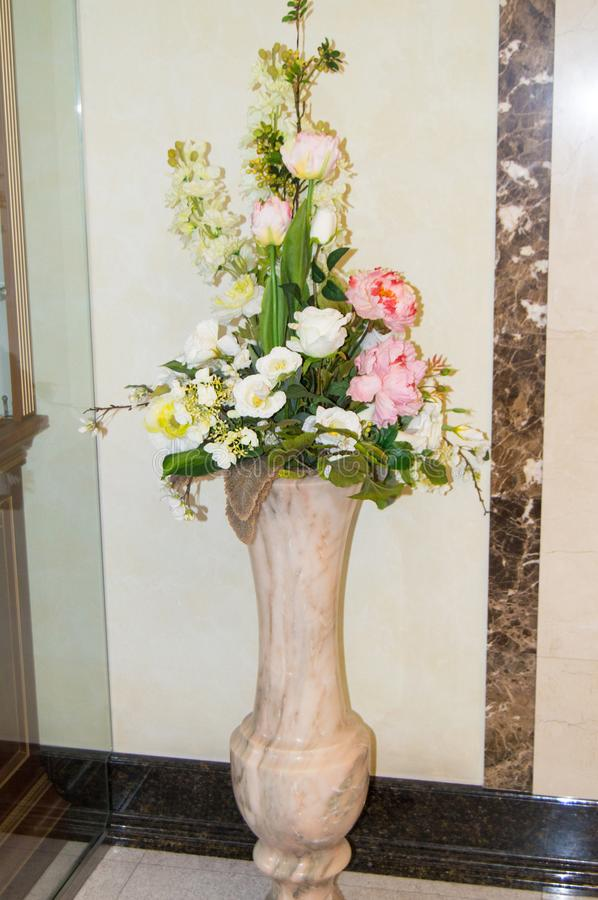 Floor marble vase with a bouquet of flowers on the background of a marble wall in the lobby of a luxury hotel. Hall, white, decor, pink, fresh, room, beautiful royalty free stock image
