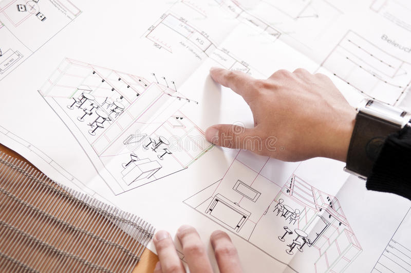Floor plan of an exhibition stand. You can see the schedule an exhibition stand in the form of a CAT drawing. It is on the table and a hand pointing to the area stock photography