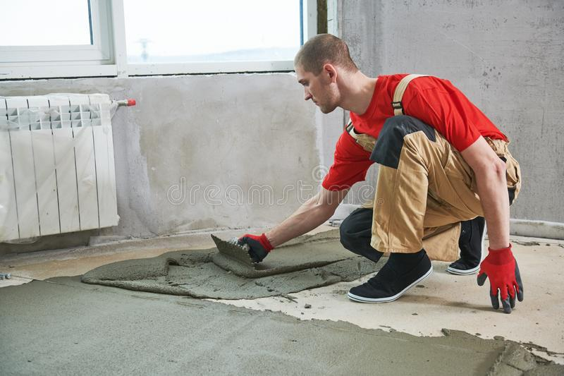 Floor cement work. Plasterer smoothing floor surface with screeder stock photos
