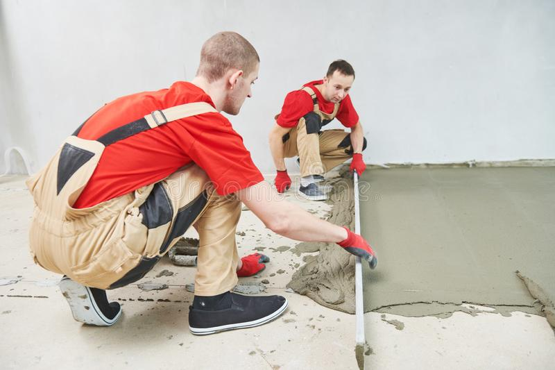 Floor cement work. Plasterer smoothing floor surface with screeder stock images