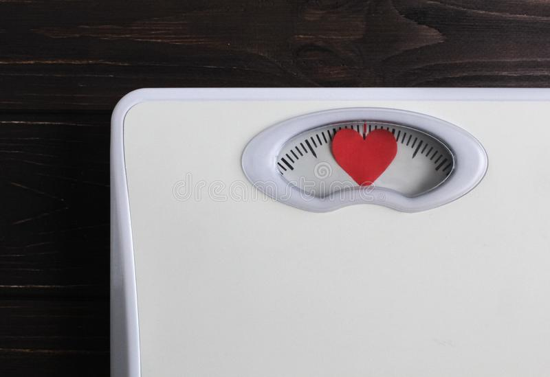 Floor scales with heart instead of numbers. Love your body concept. Fitness lifestyle motivation. Wooden background royalty free stock images
