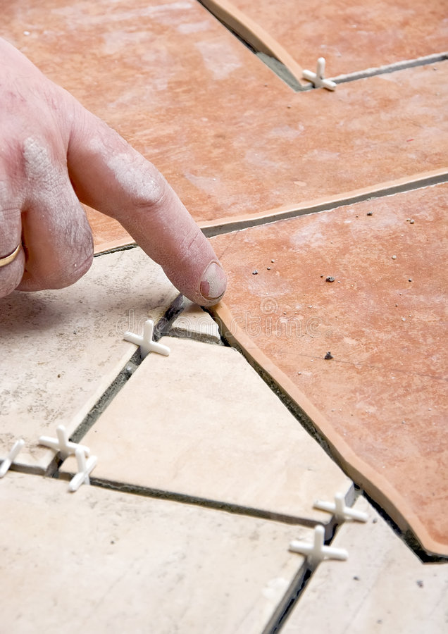 Floor tiles installation. A construction worker putting on new floor tiles. Focus on his hand and tiles gaps royalty free stock photo