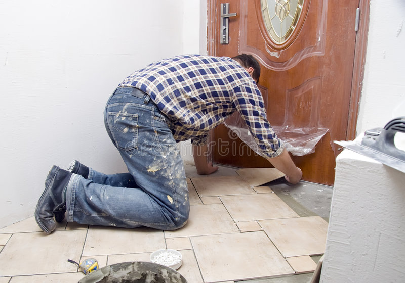 Floor tiles installation. A construction worker putting on new floor tiles royalty free stock photography