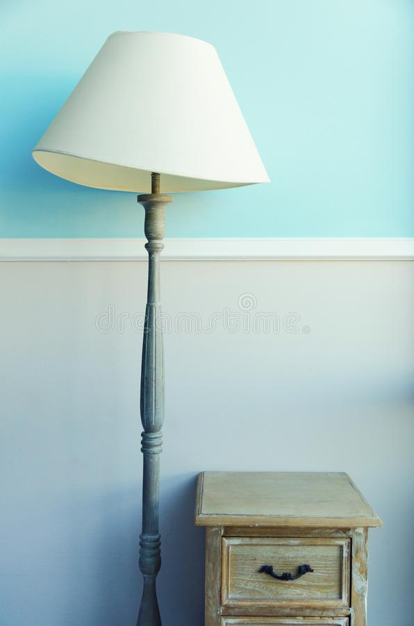 Floor torch lamp, wooden nightstand, curtains on pastel blue wall background. Banner with copy space. Minimalistic room interior stock photography