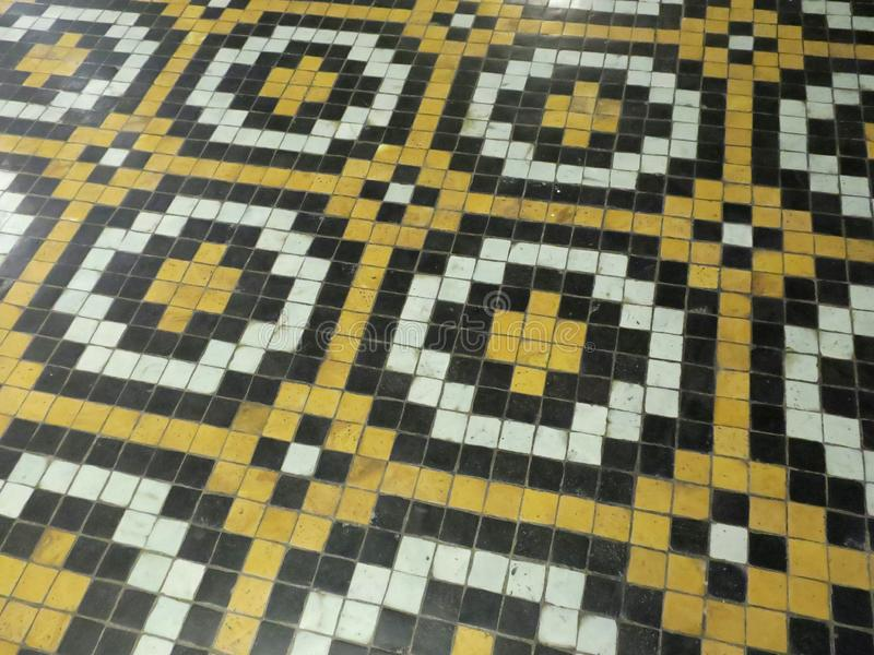 Floor of yellow black and white tiles forming crosses and a moving pattern royalty free stock photos