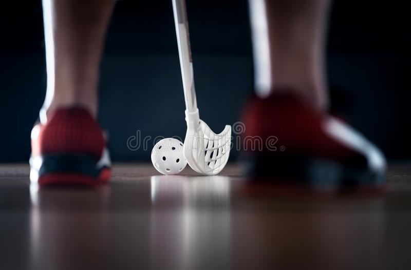 Floorball player standing with stick and ball on. Floor hockey. Back view between sneakers. Dramatic light. stock images