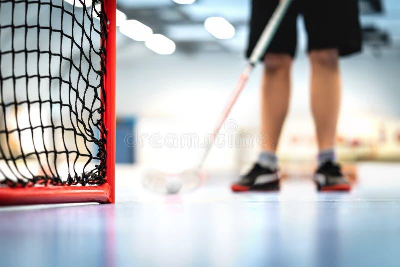 Floorballdoel en netto Speler opleiding op de achtergrond Hockey van de mensen het speelvloer stock foto's