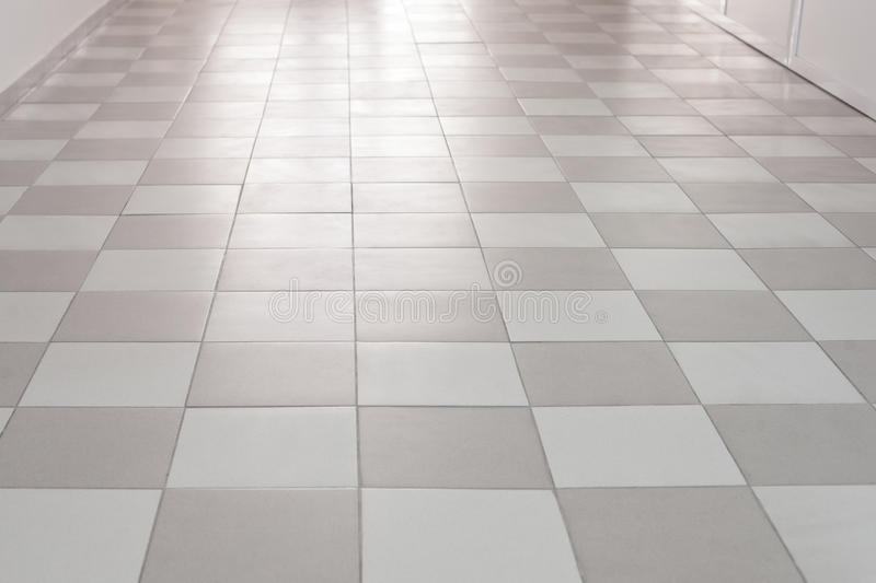 Flooring tiles moving away in perspective. Flooring tiles in the hutch looks like a chess board, goes forward, moving away in perspective, and light is visible stock images