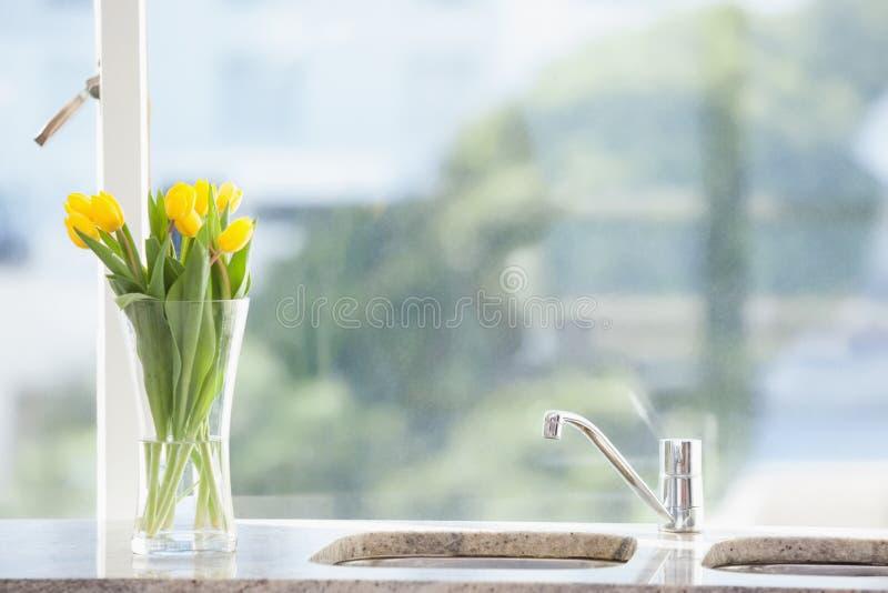Flor amarela em um vaso no dissipador imagens de stock royalty free