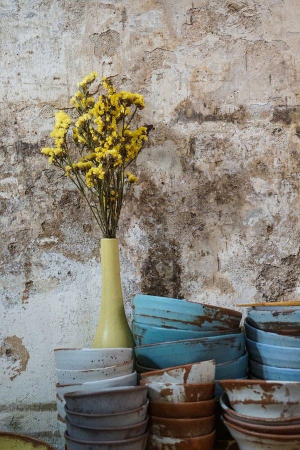 A flor amarela em uma argila cerâmica azul do vaso rola, placas imagens de stock