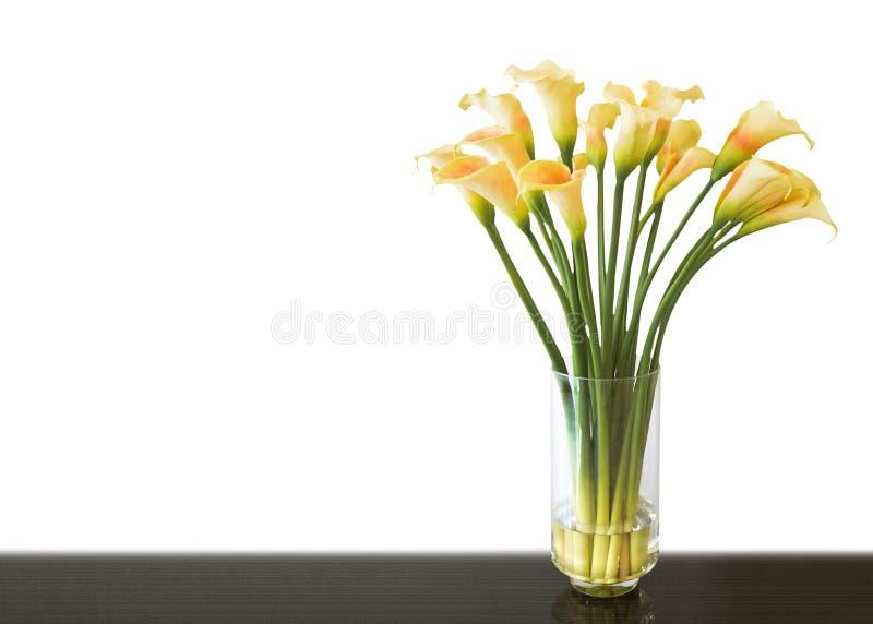 Flor amarilla de la cala en florero imagenes de archivo