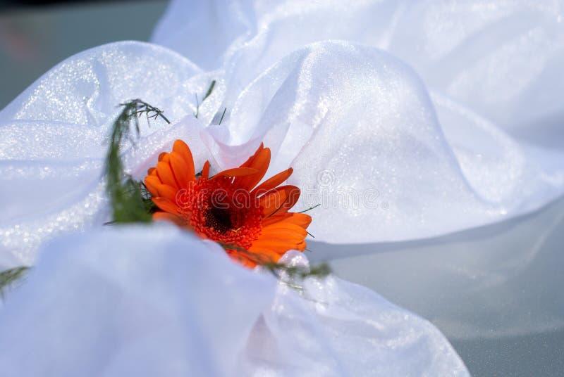 Flor anaranjada de la boda en el satén blanco foto de archivo