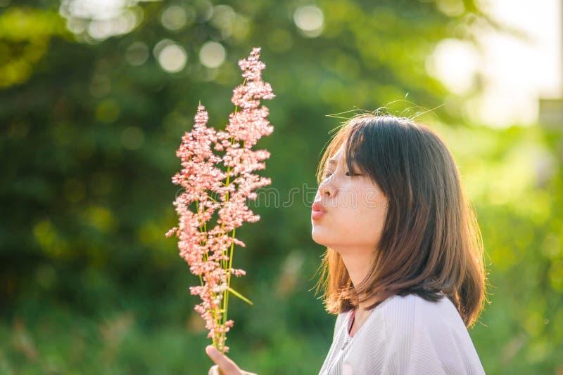 Flor asiática de la hierba del ventilador de la muchacha del adolescente con el sol foto de archivo