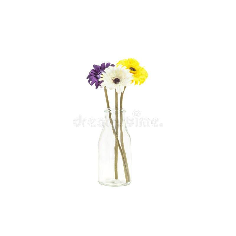 Flor colorida artificial de la tela del primer en la botella de cristal transparente aislada en el fondo blanco fotografía de archivo