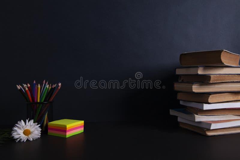 Flor con los libros en su mesa imagen de archivo