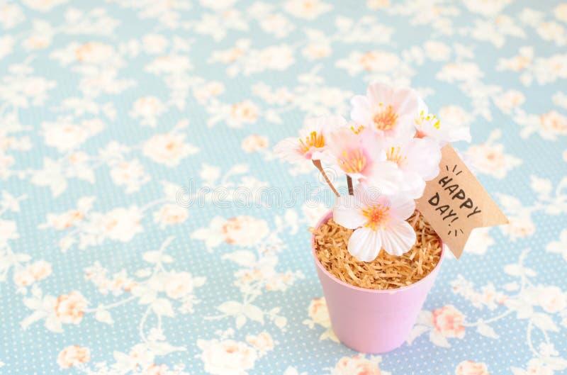 Flor cor-de-rosa animador artificial no potenciômetro de aço pequeno com dia feliz imagens de stock