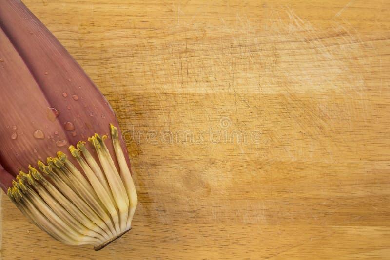 Flor da banana com água no fundo de madeira fotos de stock royalty free