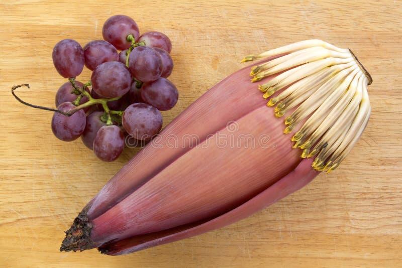 Flor da banana e uva roxa no fundo de madeira imagem de stock
