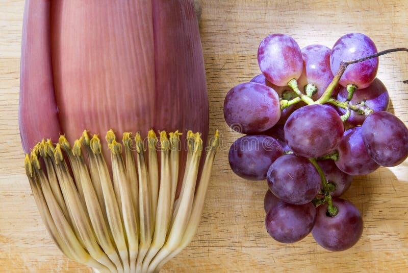 Flor da banana e uva roxa no fundo e na iluminação de madeira imagem de stock royalty free