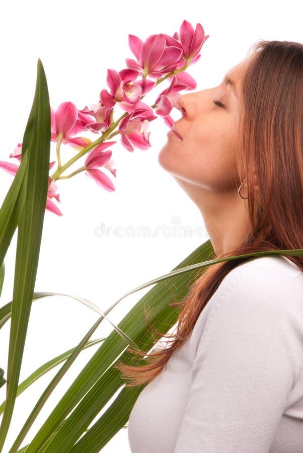 Flor de cheiro bonita da orquídea da mulher nova fotos de stock royalty free