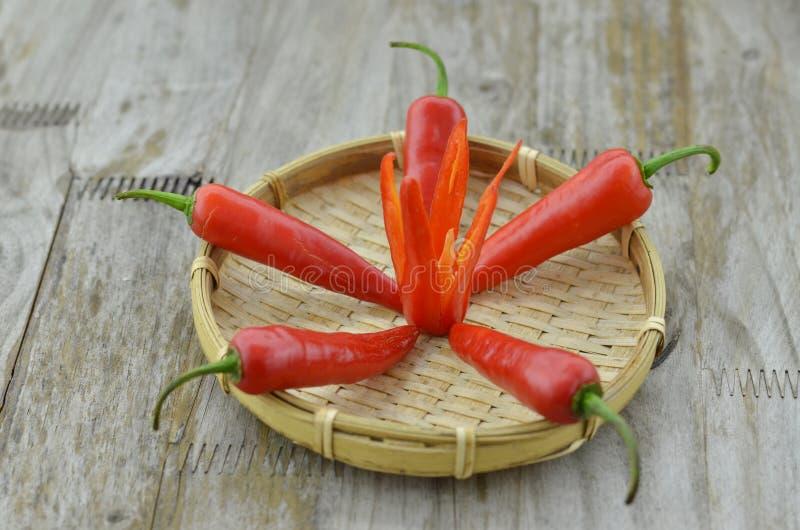 Flor de corte candente de las pimientas de chile en cesta en fondo de madera fotografía de archivo