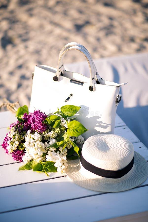 Flor de la lila Sombrero elegante del verano con una cinta y un ramo de flores de la lila en un fondo azul foto de archivo libre de regalías