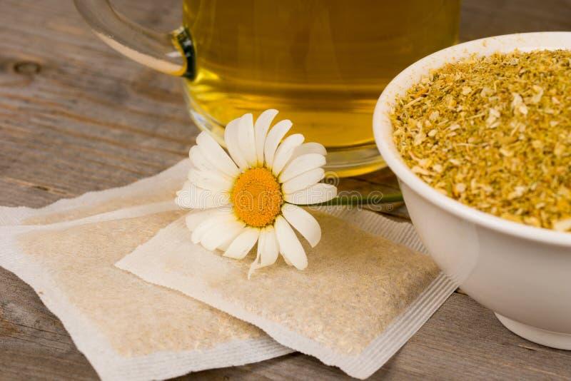 Flor de la manzanilla con té caliente y plantas secadas imagenes de archivo