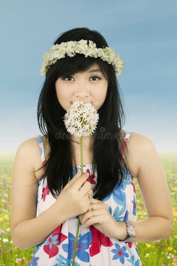 Flor de la primavera de la mujer que huele linda foto de archivo