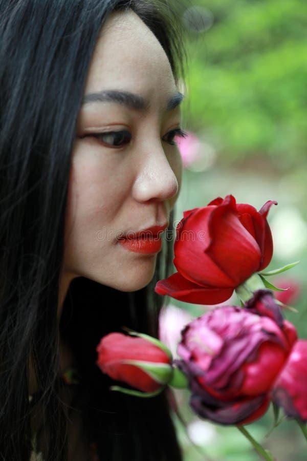 Flor de la rosa del rojo de la mujer que se besa modelo hermosa imagen de archivo