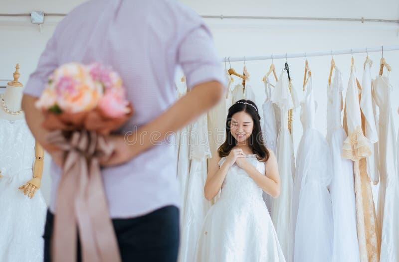 Flor de ocultación del novio detrás de detrás para sorprender a la novia, emoción positiva de la mujer y hacerla frente asombrado foto de archivo libre de regalías