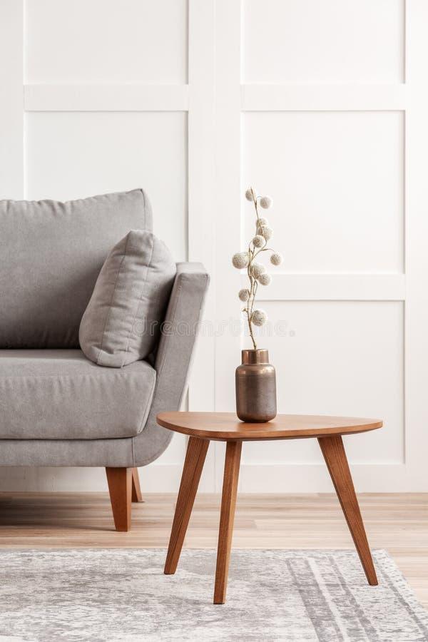 Flor del algodón en el florero de cobre elegante en la pequeña mesa de centro de madera al lado del canapé gris imagen de archivo
