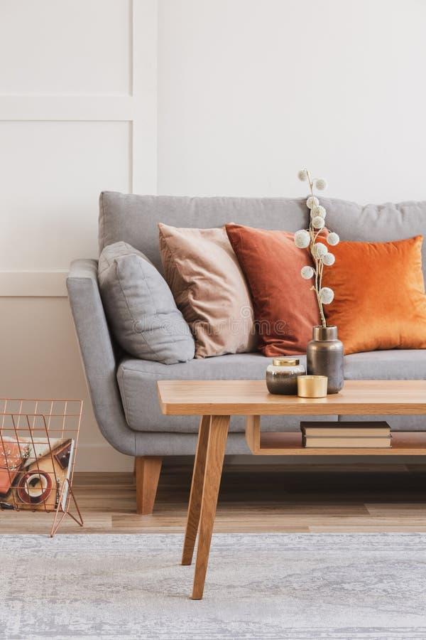 Flor del algodón en el florero de cobre elegante en la pequeña mesa de centro de madera al lado del canapé gris fotografía de archivo libre de regalías