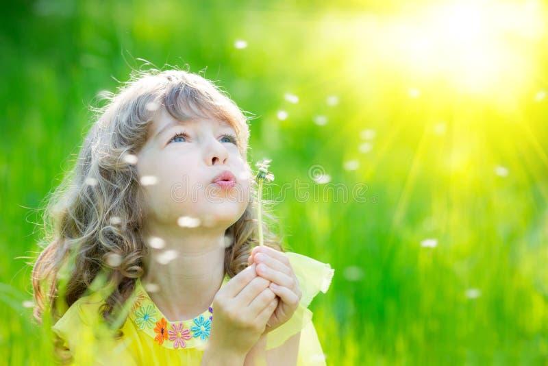 Flor del diente de león del niño que sopla feliz al aire libre imagen de archivo