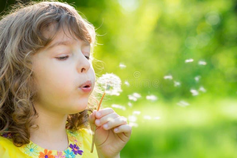 Flor del diente de león del niño que sopla feliz al aire libre imagen de archivo libre de regalías