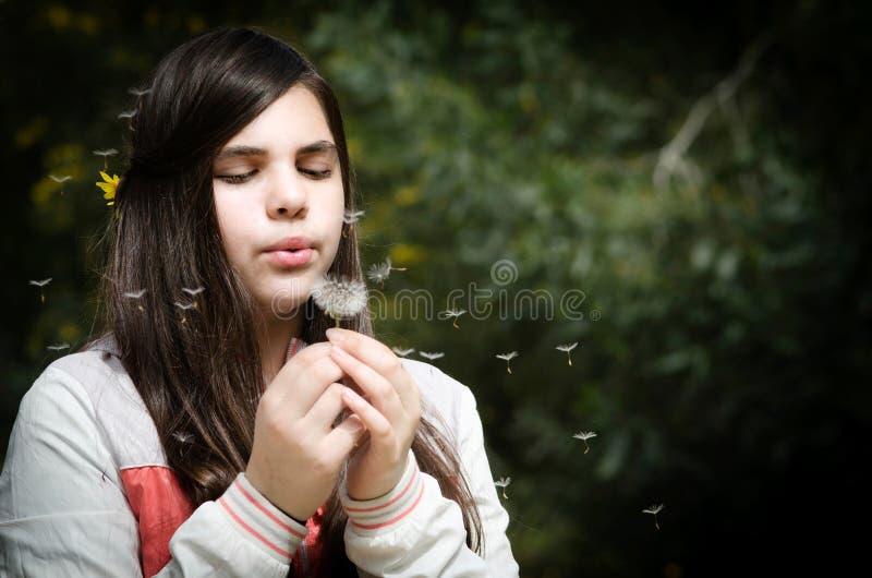 Flor del diente de león de la muchacha que sopla hermosa joven fotos de archivo libres de regalías