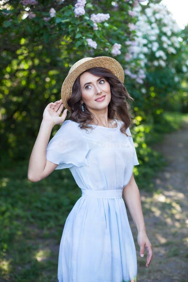 Flor del resorte Señora femenina hermosa con el pelo oscuro en un sombrero de paja en un fondo del jardín verde La felicidad exte imagen de archivo