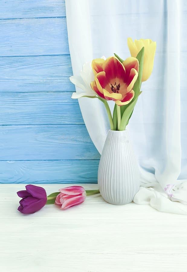 Flor del tulipán en un saludo de la elegancia del florero en fondo de madera fotografía de archivo