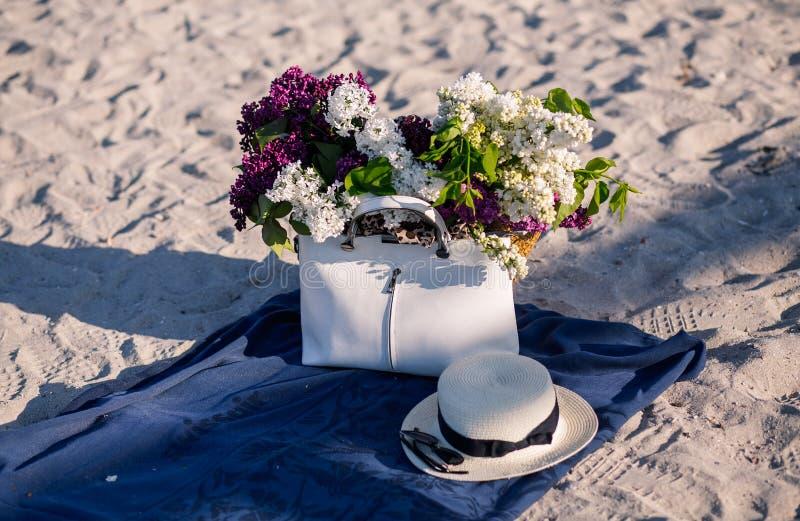 Flor do lil?s Chapéu do verão das mulheres com uma fita e um ramalhete de flores lilás em um fundo azul Vista superior Configura? imagem de stock
