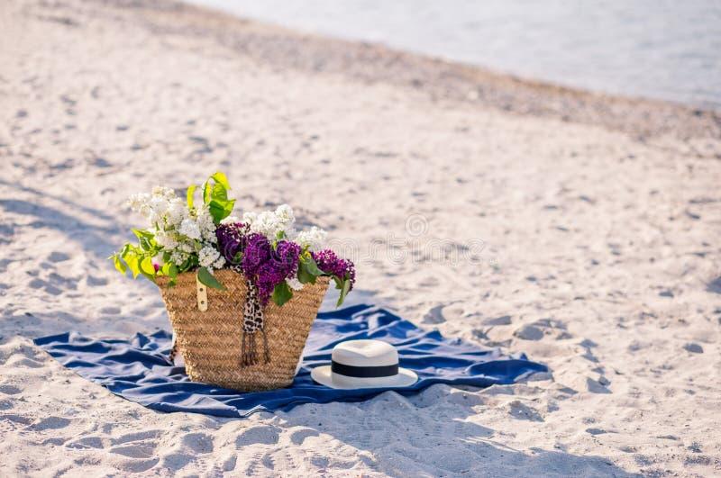 Flor do lil?s Chapéu do verão das mulheres com uma fita e um ramalhete de flores lilás em um fundo azul Vista superior Configura? imagens de stock royalty free