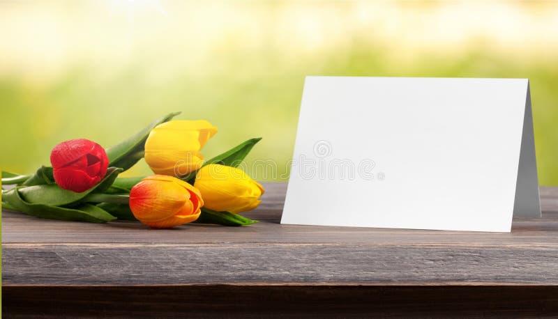 Flor e cartão na mesa imagem de stock