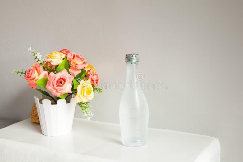 Flor e garrafa da água, na tabela branca foto de stock