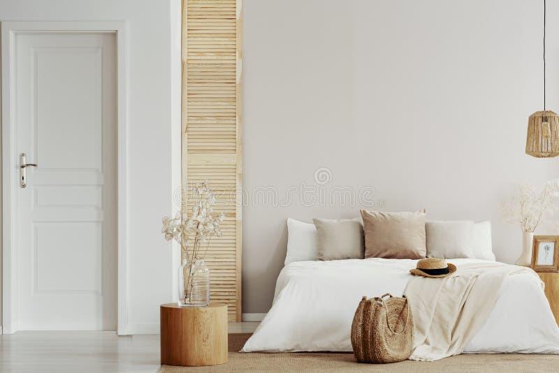 Flor en el florero de cristal en la tabla de madera redonda en el dormitorio natural beige, espacio de la copia en la pared vacía imagen de archivo libre de regalías