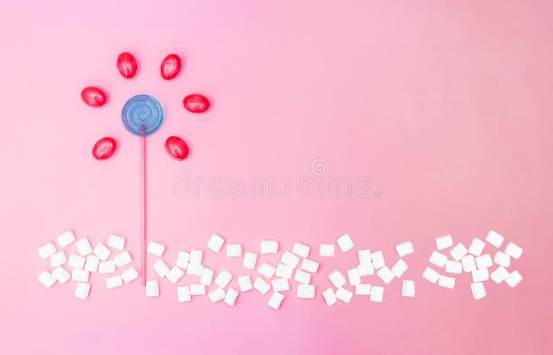 Flor feita do pirulito e dos doces no fundo cor-de-rosa com espaço da cópia Configura??o lisa fotografia de stock royalty free